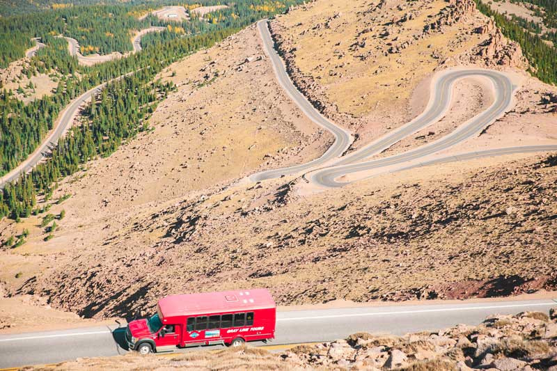 pikes peak tour by gray line red bus going up highway